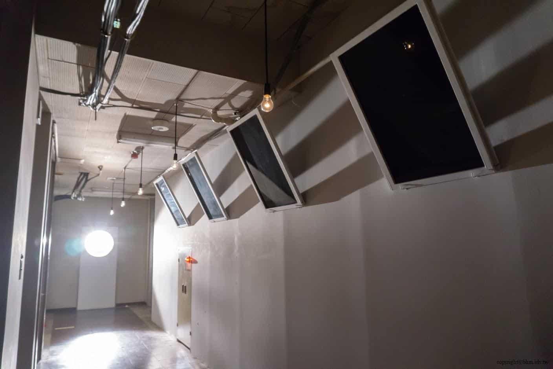 克利斯蒂安‧波爾坦斯基+將‧卡爾曼,最後的教室,教室走廊遠方強燈將一旁沒有照片相框凸顯出來。更走進一點,強光下有著說不出來詭異 最後的教室 最後的教室 the last class 04